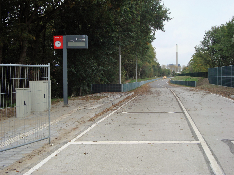 De bushalte Groeneweg in aanleg halverwege de vroegere stations Velsen Zeeweg en Velsen/IJmuiden Oost gezien in de richting van Velsen-IJmuiden Oost op 27 oktober 2016. Op de achtergrond de Nuon-schoorsteen. Er is een geasfalteerd tracé aangelegd inclusief geluidswal en -schermen. Foto: Hans Brouwer.