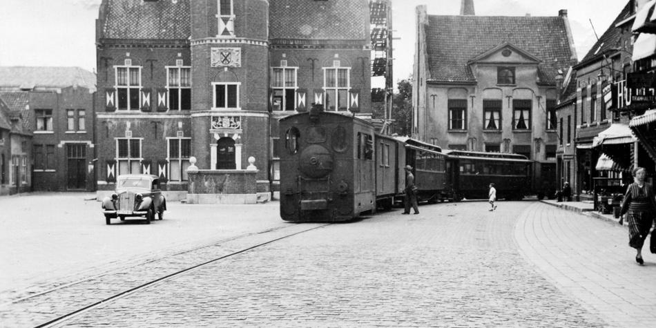 Zo reed de tram van de Maas-Buurtspoorweg door Gennep. Ondanks dat de auteur de tram zelf niet heeft meegemaakt, vond hij voldoende oud-medewerkers die het trambedrijf voor hem tot leven konden brengen. Op de foto stoomlocomotief MBS 46 met bagagewagen, twee rijtuigen en minstens een goederenwagen op de halte Markt voor het stadhuis van Gennep op 18 juli 1941. Fotograaf onbekend, collectie NVBS Railverzamelingen.