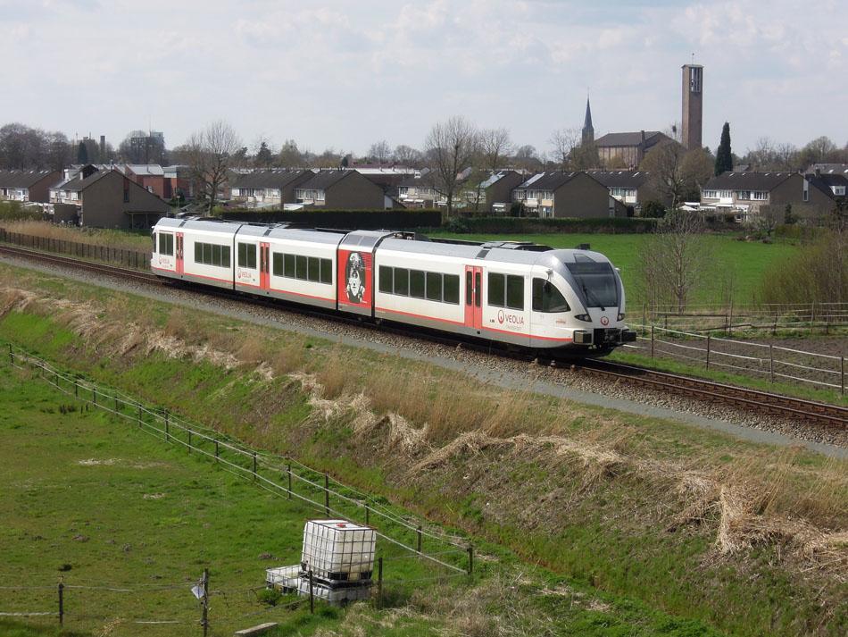De dieseldienst Nijmegen – Roermond gaat over naar Arriva, het materieel krijgt voor zover nu bekend de Arriva-huisstijl. GTW 357 van Veolia ten noorden van Tegelen op 9 april 2016. Het portret op het treinstel is van zanger/musicus/schrijver Gé Reinders. Foto: Roelof Hamoen.