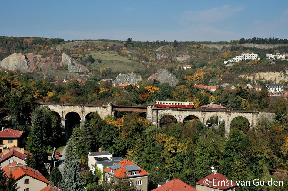 <i>Een motorwagen van de reeks 831 (831.117-7/M262.1117) van de museumclub KŽC passeert een van de bruggen, die deel uitmaakt van de Praagse Semmering op weg naar Hostivice op 19 oktober 2010. Onder het metalen brugdeel van dit vaduct loopt de andere spoorlijn. Op de achtergrond is een klein stukje van dezelfde lijn te zien. De ritten zijn een echte aanrader. Foto: Ernst van Gulden.</i>