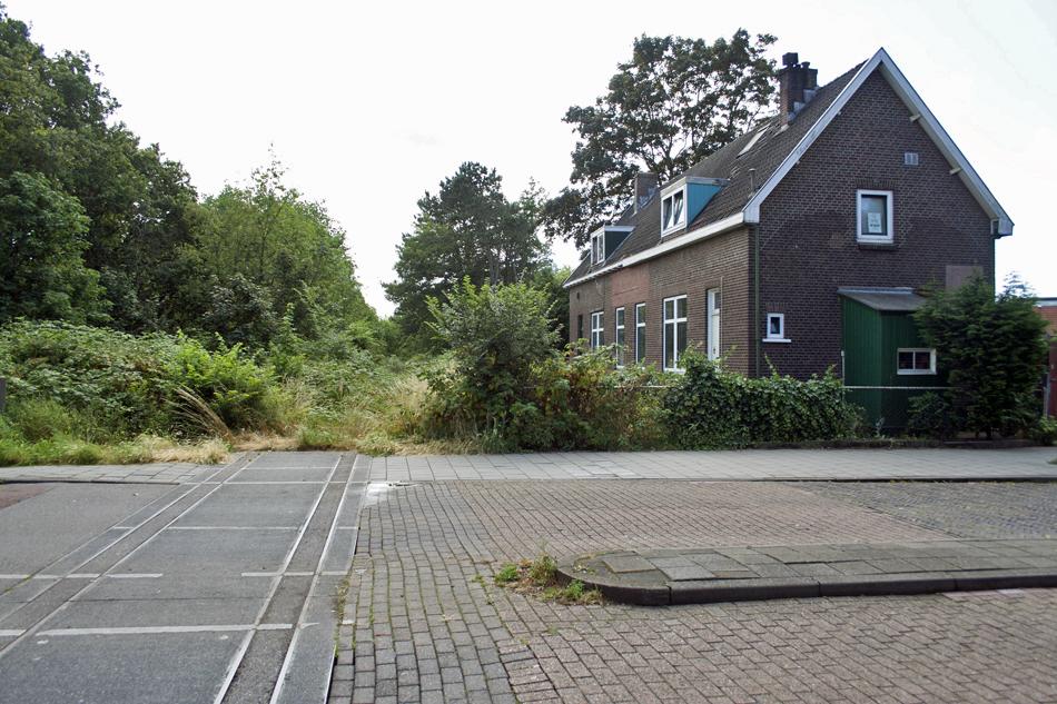De wachterswoning en de overweg in de Groeneweg gezien in de richting van Santpoort op 30 juni 2014. De rails zijn uit de overweg verwijderd, maar daarachter liggen ze nog onder de begroeiing. Foto: Oege Kleijne.