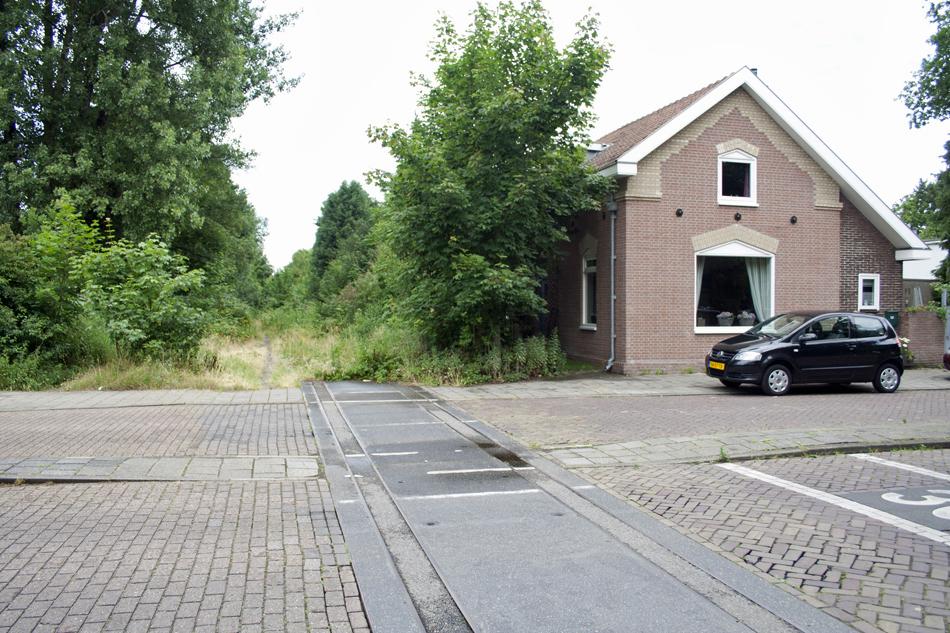 De situatie te Driehuis-Westerveld op 30 juni 2014 met de blik in de richting van Velsen Zeeweg. Behalve in de overweg liggen de rails hier nog en is de (overweg)wachterswoning rechts duidelijk herkenbaar. Foto: Oege Kleijne.