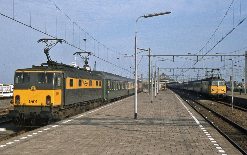 Hoek van Holland Haven vormde het begin- en eindpunt van veel internationale treinen. Op deze foto van Roelof Hamoen staan links loc 1501 met de Rhein Express (D 215) naar Oostenrijk en rechts locomotief 1306 met de Holland-Scandinavië Express (D 231) naar Denemarken in Hoek van Holland Haven. Opnamedatum: 26 juli 1979.