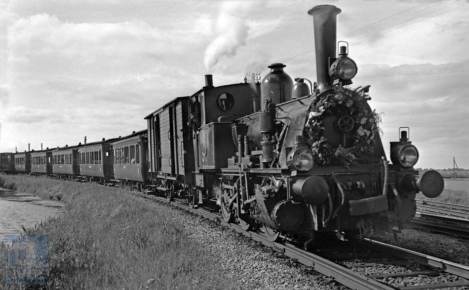 Ook na de Tweede Wereldoorlog reden er op verschillende trajecten nog stoomlocomotieven, maar hun dagen waren geteld. Dat gold bij de tramlijn Alkmaar – Bergen aan Zee niet alleen voor het materieel, ook de tramlijn zelf werd in 1955 gesloten. NS-reizigerstram 64, met locomotief 7744, rijdt op 25 juni 1949 langs Koedijk Splitsing in de richting van Alkmaar (rechts is nog net het aftakkend tramspoor te zien naar Schoorl en Warmenhuizen (ooit door naar Schagen). De locomotief is versierd met een krans ter gelegenheid van het 40-jarig bestaan van de tramlijn Bergen Binnen – Bergen aan Zee (geopend op 25 juni 1909).