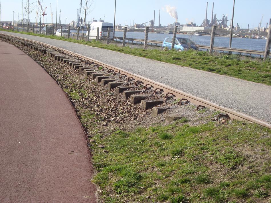In de boog bij Velsen-IJmuiden Oost liggen de rails nog. Op de achtergrond onder meer de Hoogovens (Tata Steel) en het Noordzeekanaal. Vanaf dit punt liep de lijn parallel aan het water.