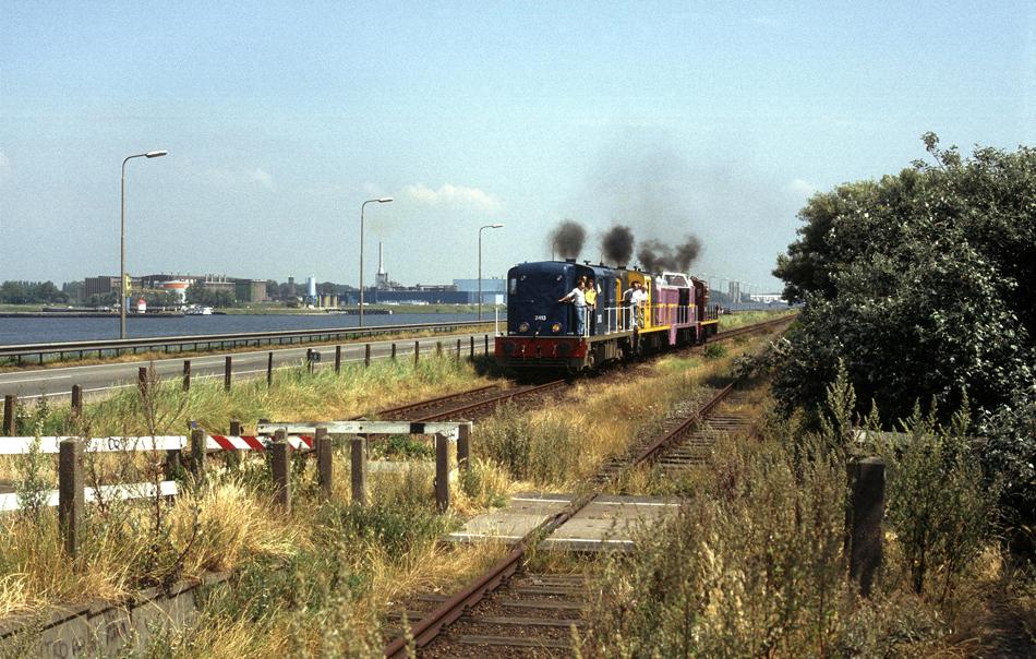 De vroegere halte IJmuiden Casembrootstraat met de diesellocomotieven 2413, 2444, 2530 en 2450 op 4 augustus 1991, tijdens een rit door Noord-Holland als beloning voor de NVBS'ers die deze 2400-en hebben geschilderd voor de afscheidsexcursie van deze locomotiefserie. Foto: Roelof Hamoen.