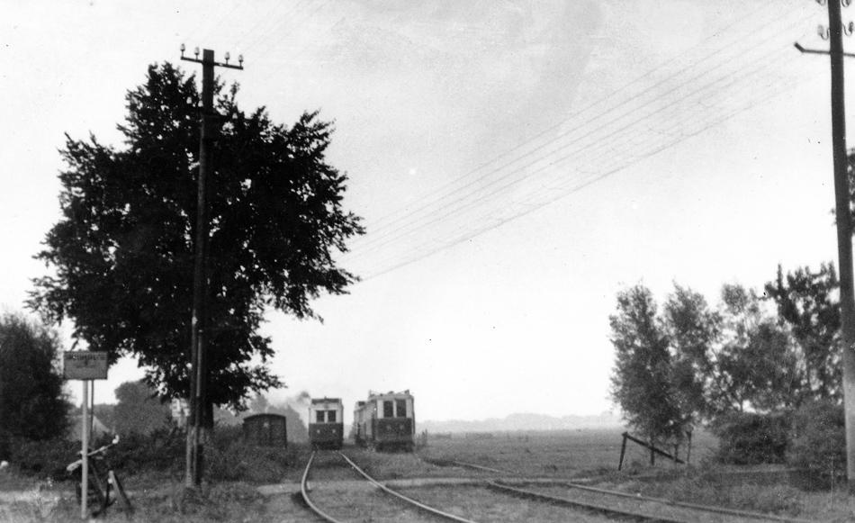"""Een wat onscherpe maar wel bijzondere foto, ook tijdens diezelfde fietstocht in september 1939 gemaakt, van de dubbelsporige trambaan bij """"de Stolp"""" met de nog geen tien jaar oude motorrijtuigen. We kijken hier in de richting van Muiderberg. In 1932 was op deze plek een nieuwe dubbelsporige trambaan in gebruik genomen. Links van het bord met de fiets liep de vroegere enkelsporige tramlijn parallel aan de Naarder Trekvaart in de richting van Muiden en Amsterdam. Tot op vandaag de dag is deze plek nog in het landschap terug te vinden. Foto: Jacobus Meulman."""